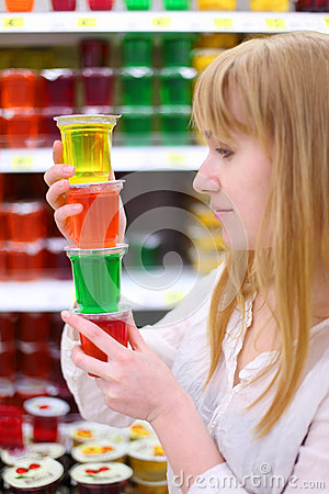 Blonde girl keeps multi-colored jelly in store
