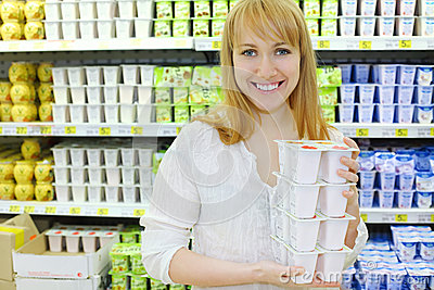 Blonde girl keeps yoghurt in shop