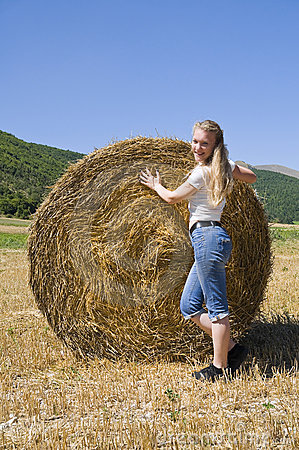 Blonde girl leaning against a rolling haystack.
