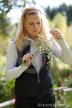 Blonde girl looks at the bouquet of daisies