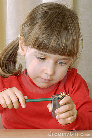 Blonde girl sharpening a pencil.