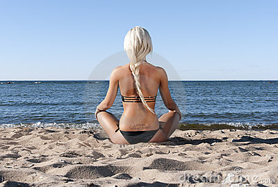 Blonde girl sits on the beach and meditate Stock Photo
