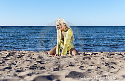 Blonde girl sits near the sea on his knees