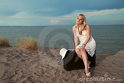 Blonde girl sitting on a suitcase at the beach