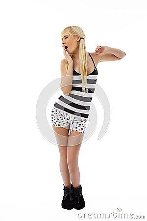 Blonde girl standing in pajamas and yawning
