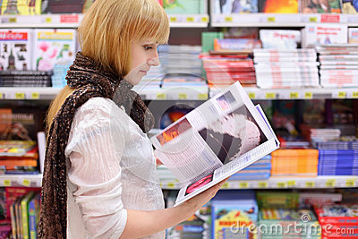 Blonde girl thumbs book in supermarket