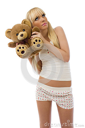 Blonde girl wearing pajamas embraces teddy bear