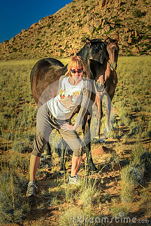 Blonde girl and wild horses