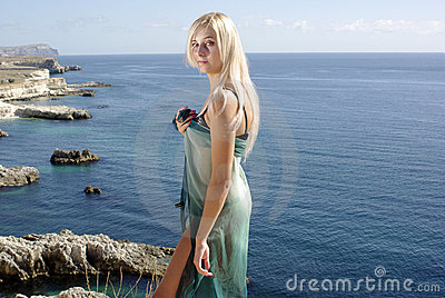 Blonde in green pareo  on rocky beach near sea