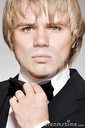 Blonde heer in elegant zwart kostuum met boog-band
