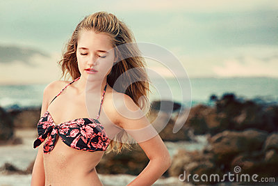 Blonde lady closes her eyes in the wind on the beach