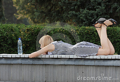Blonde laying down on bench