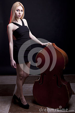 Blonde model next to a broken contrabass