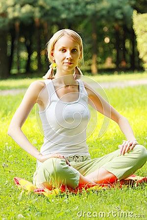 Blonde in park legs crossed