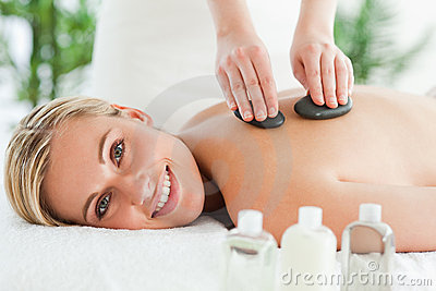 Blonde smiling woman experiencing a stone therapy