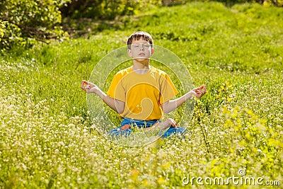 Blonde teen boy in a lotus position meditating, meditation on na