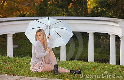 Blonde with umbrella is relaxing in autumn park