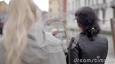 Blonde und brunette junge Frauen gehen zusammen in Stadt in der Tageszeit entlang Damm von Fluss, hintere Ansicht stock video