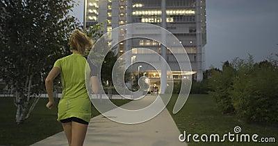 Blonde vrouw in geschiktheidsslijtage lopende opleiding op parkgang Achter na mening De zomeravond of nacht industrieel stock footage