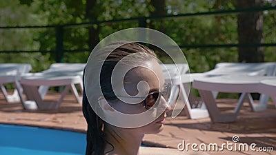 Blonde vrouw met nat haar stijgt uit het water en gaat naar de rand, glimlacht voor camera stock video