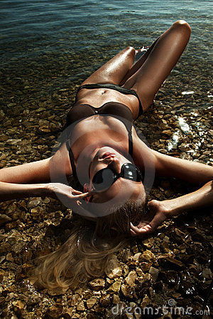 Blonde wearing sunglasses, laying in water
