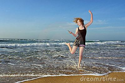 Blonde woman dancing with mobile phone on beach