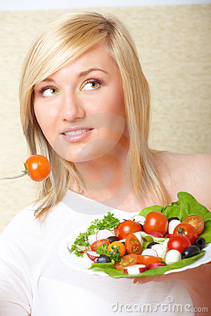 Blonde woman eating healthy food, Greek salad