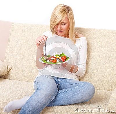 Blonde woman eating healthy food, Greek salad