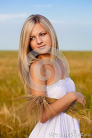 Blonde woman holding wheat sheaf