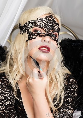 Free Blonde Woman In A Lace Mask Holding A Black Feather Near Her Face Stock Photography - 127082452