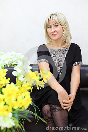 Blonde woman sits on black leather couch
