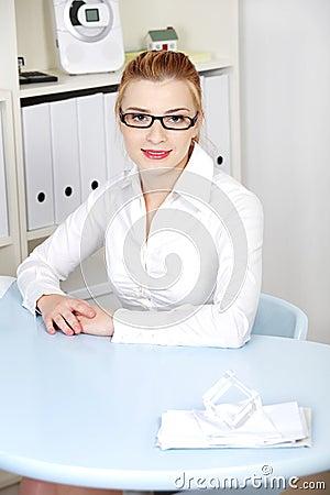 Blonde woman sitting behing the desk.