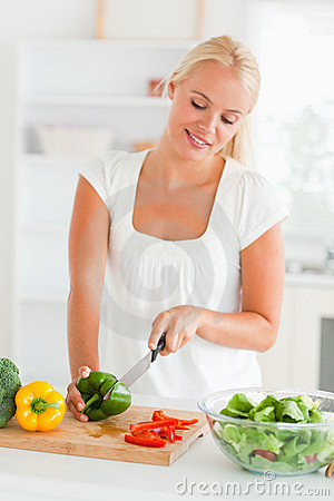 Blonde woman slicing pepper