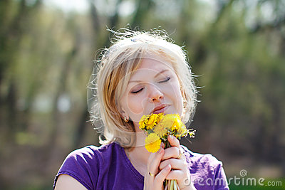 Blonde woman smell dandelion outdoor