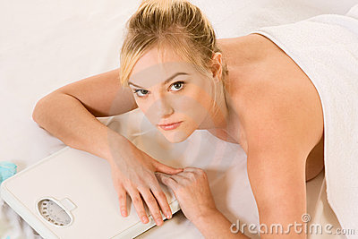 Blonde woman in spa holding on weight scales