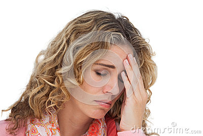 Blonde woman suffering with headache thus holding her head