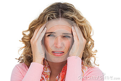 Blonde woman suffering with headache thus touching her temples