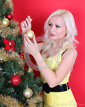 Blonde young woman decorating Christmas tree over red