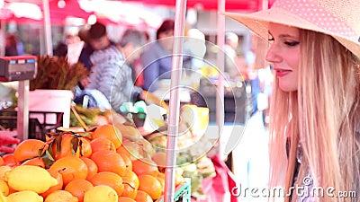 Blondemeisje bij de markt, ruikend fruit stock video