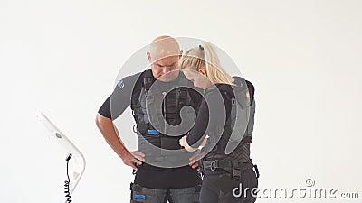 Blondes Mädchen hilft Mann, EMS-Kostüm an zu setzen stock video