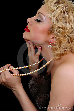 Blondie woman with pearl necklace in hand dreaming
