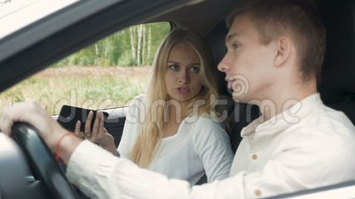 Blondynki dziewczyna i jej chłopak siedzi w samochodzie dyskutujemy, zbiory