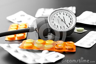 Blood pressure meter and pills on the table