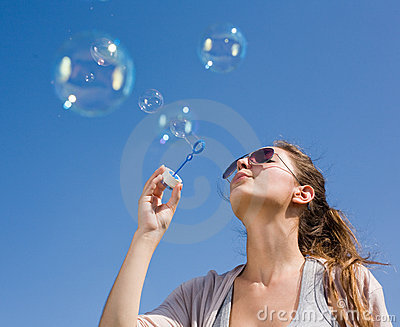 Blowing bubbles into the sky.