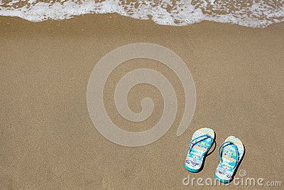 Blue beach slippers on sandy beach with copy space