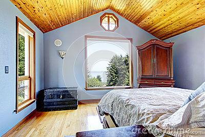 Blue bedroom with wood ceiling and bed interior.