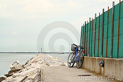 Blue bike parked by rock path leading into the sea