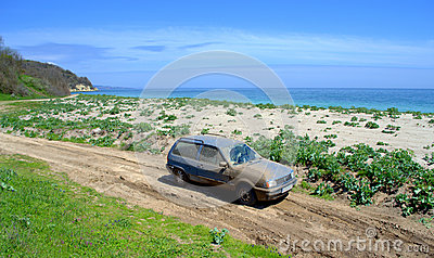Blue car covered in mud on dirt road to a beach