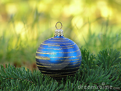 Blue christmas ball with golden swirls in green grass