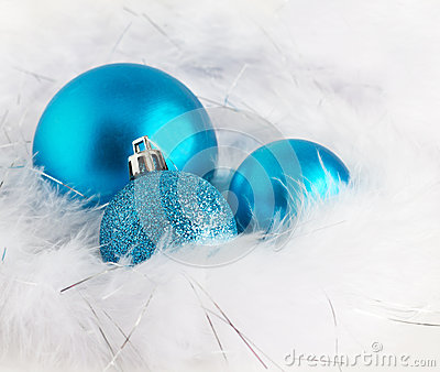 Blue Christmas baubles on soft white feathers